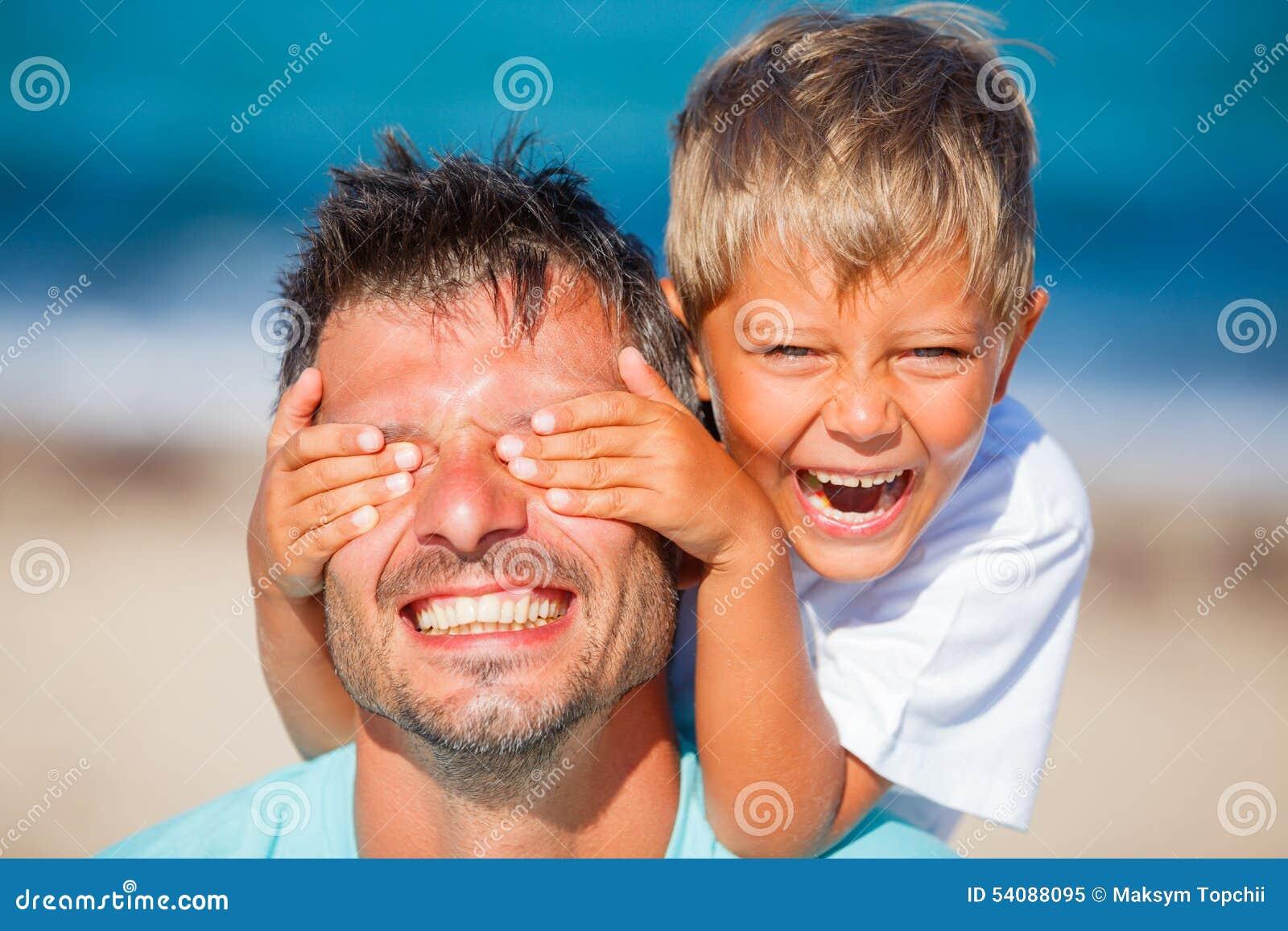Jongen met vader het spelen bij het strand