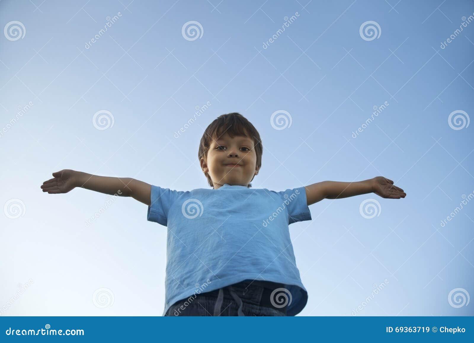 Jongen met wijd geplaatste handen op achtergrond van hemel