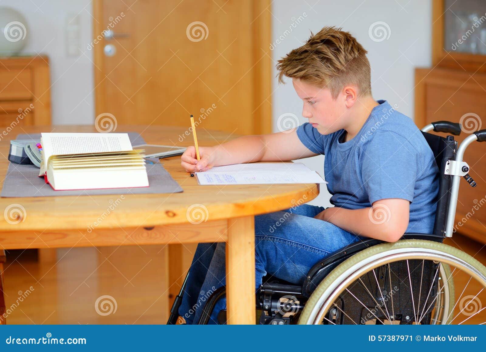 Jongen in rolstoel die thuiswerk doen