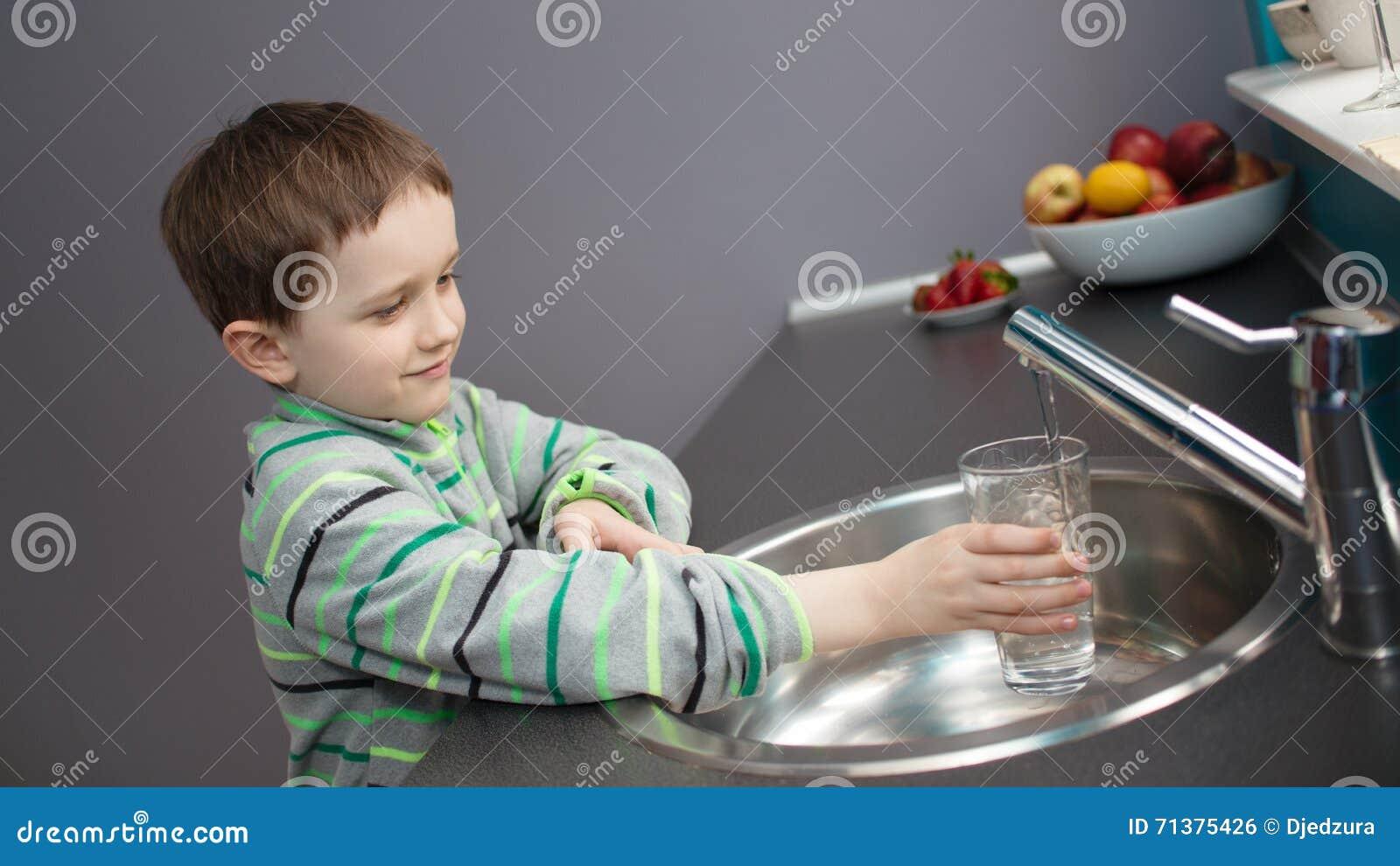 Jongens gietend leidingwater in een glas