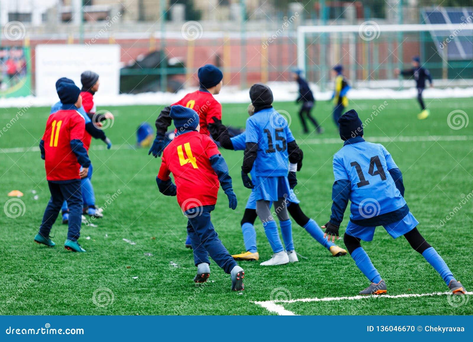 Jongens in het rode en blauwe voetbal van sportkledingsspelen op groen grasgebied Het Spel van de de jeugdvoetbal De concurrentie