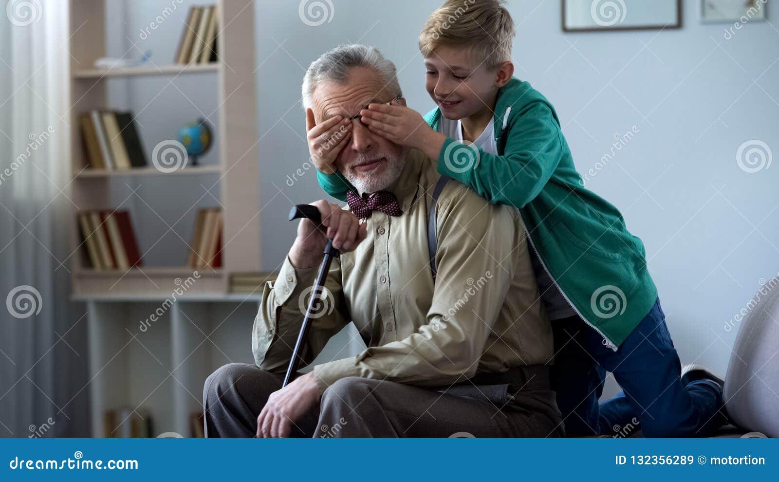 Jongens speel en sluitende grootvader samen in het weekend ogen, die pret hebben