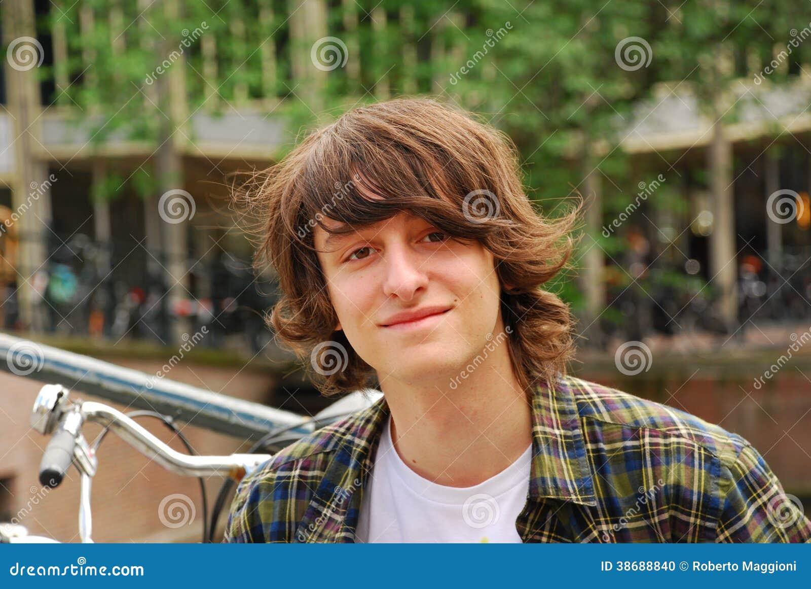 Jongensportret, 16 jaar oude tiener met lang haar