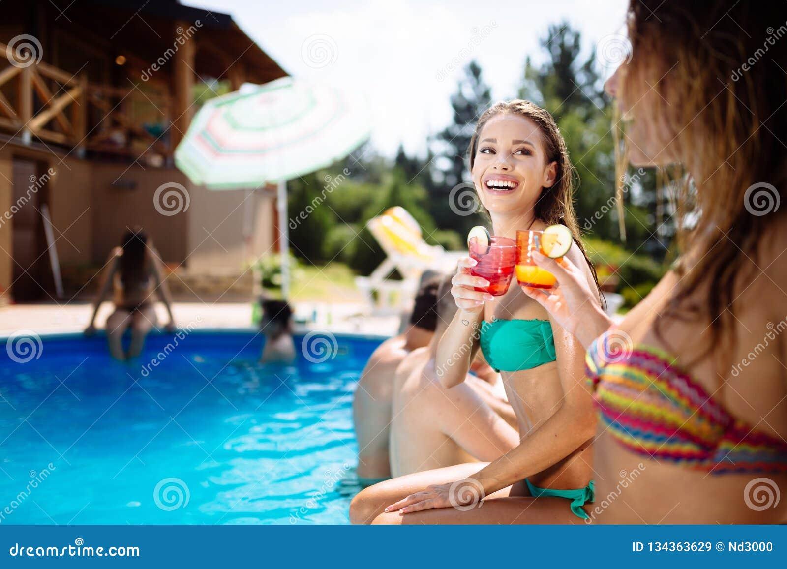 Jongeren die cocktails drinken bij zwembad
