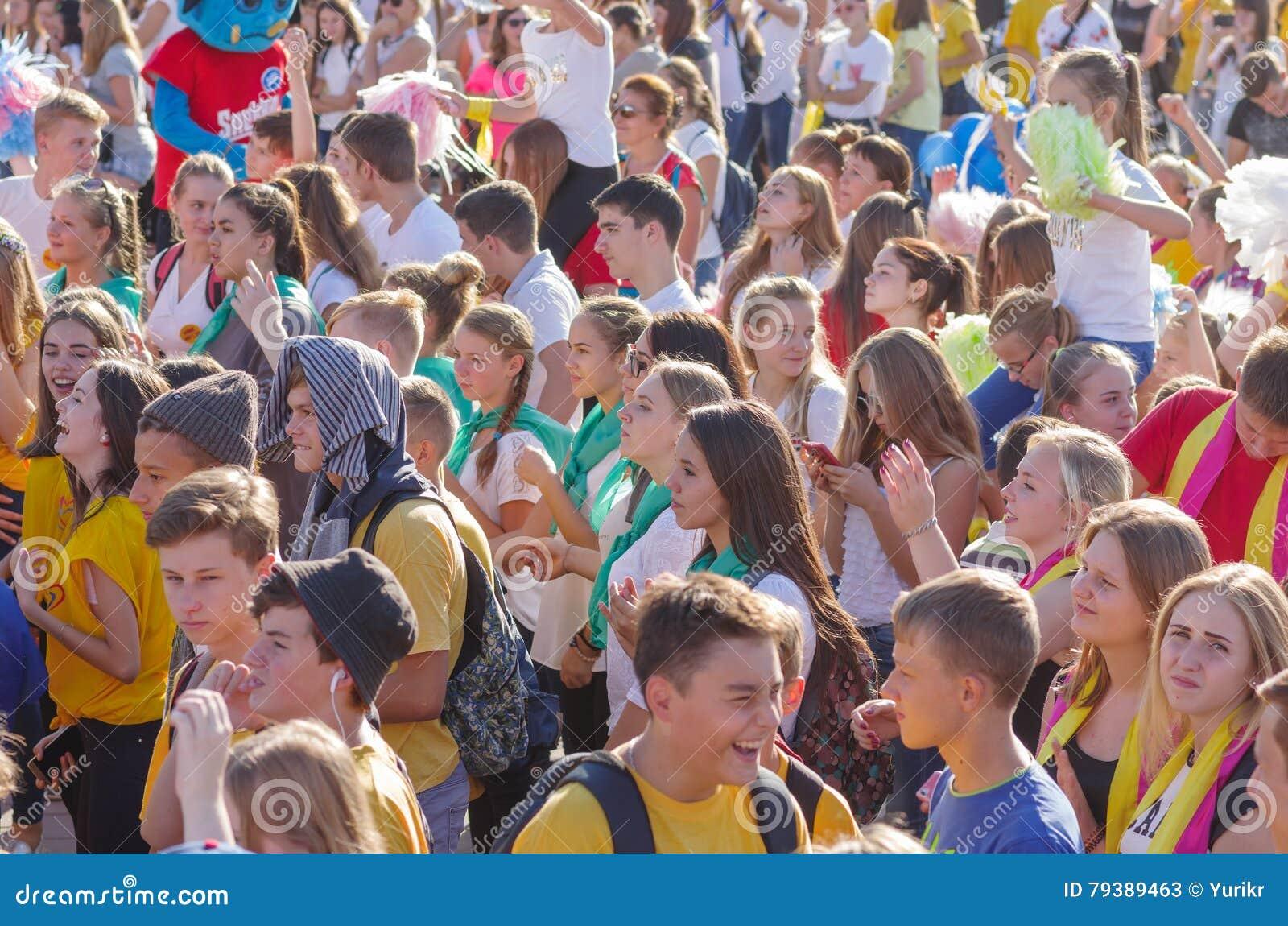 Jongerengezichten met positieve emoties terwijl muziek op de de rivierdijk van Dniepr luister