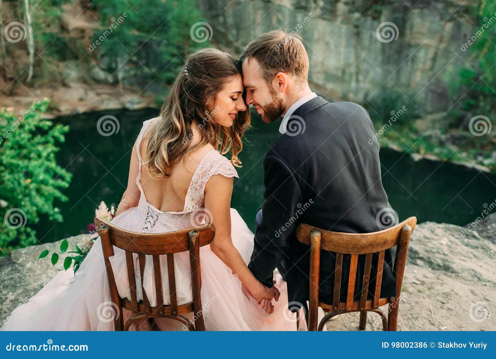 Jonggehuwden die bij de rand van de canion en het paar zitten die elkaar met tederheid en liefde kijken Bruid en bruidegom