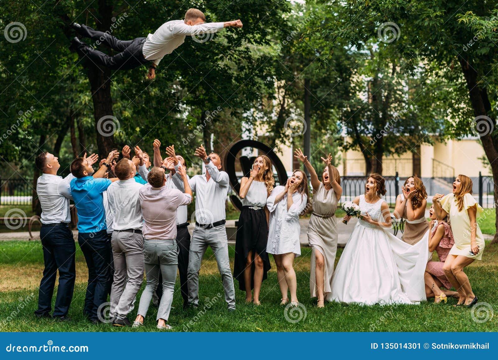 Jonggehuwden en gasten die pret hebben bij het huwelijk