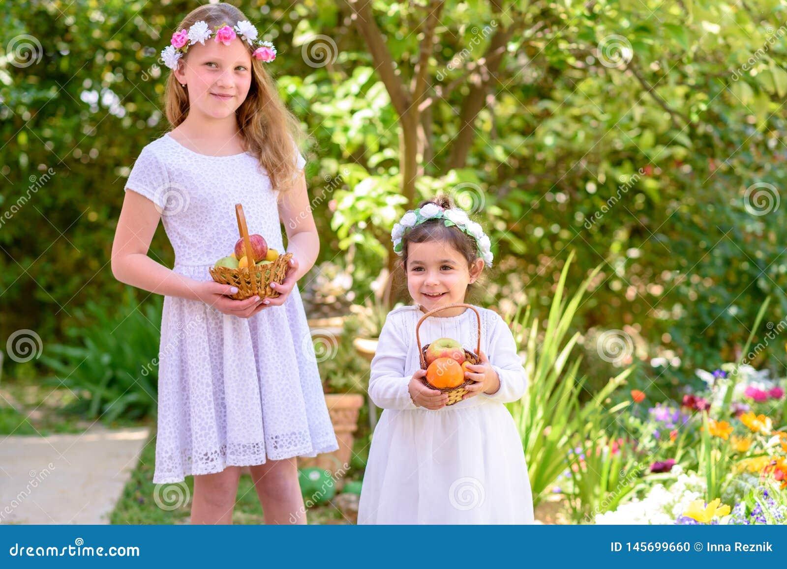 Joodse vakantie Shavuot De HarvestTwomeisjes in witte kleding houdt een mand met vers fruit in een de zomertuin
