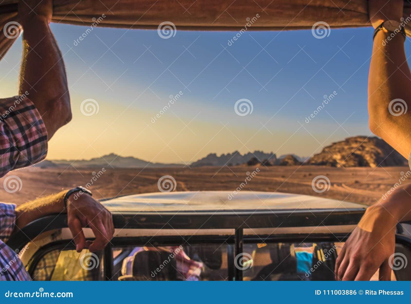 Jordan rumu wadi desert dwa turysty pozwolą jechać wokoło w dżipie przez pustyni przy zmierzchem, kontrolującym beduin