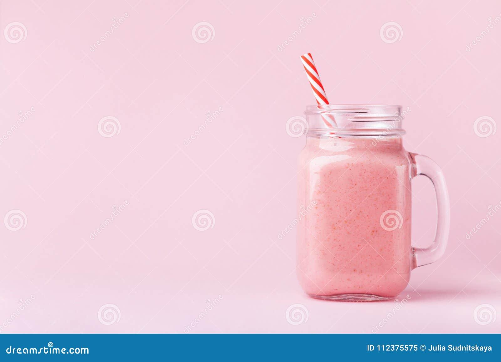 Jordgubbesmoothie eller milkshake i murarekrus på rosa pastellfärgad bakgrund Sund mat för frukost och mellanmål
