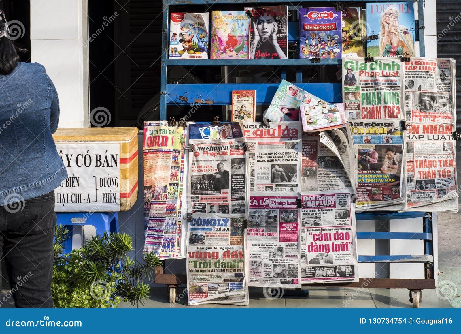Jornais e compartimentos vietnamianos em um suporte em uma rua de Ho Chi Minh City em Vietname