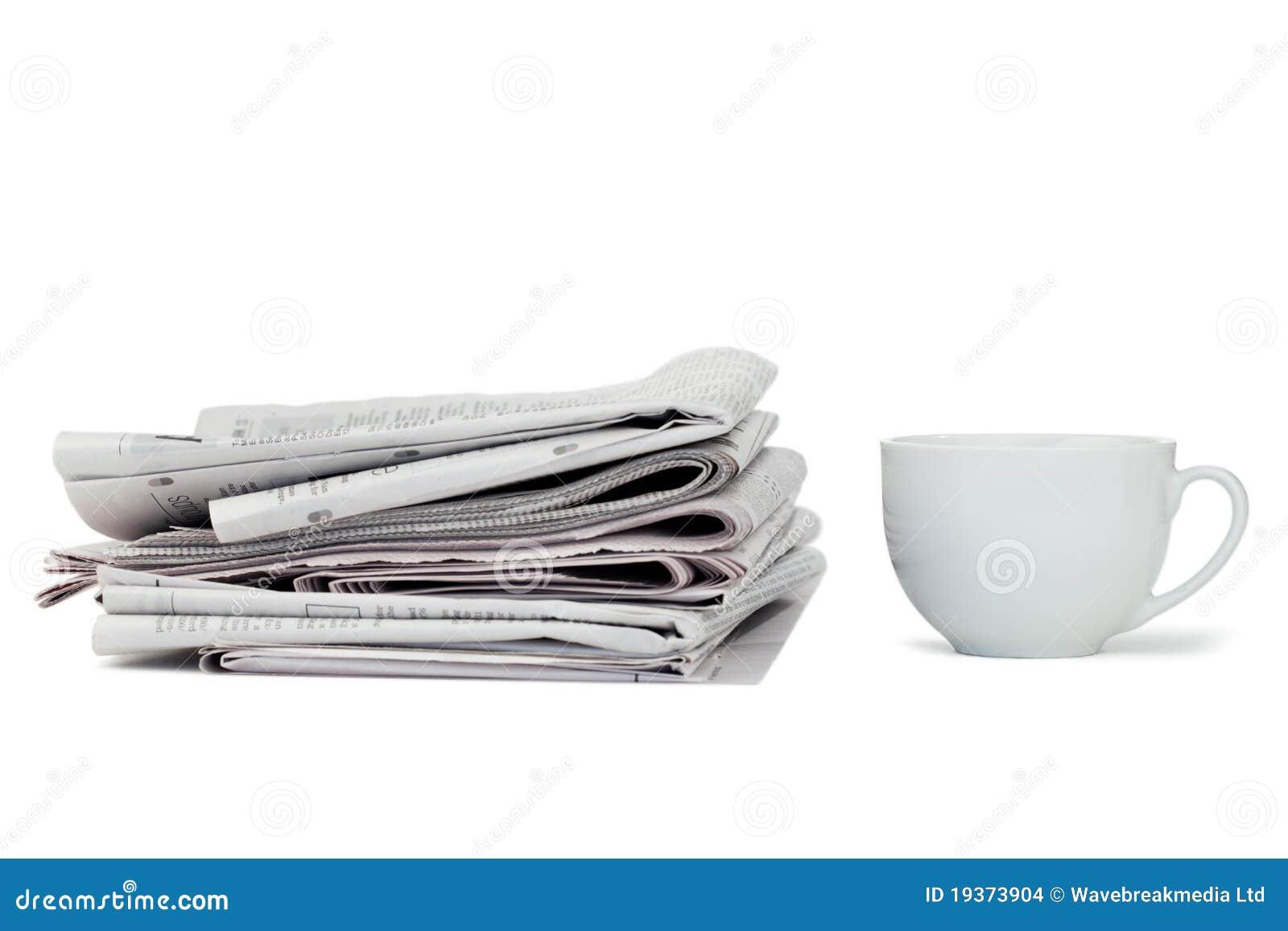 Jornais e copo do chá