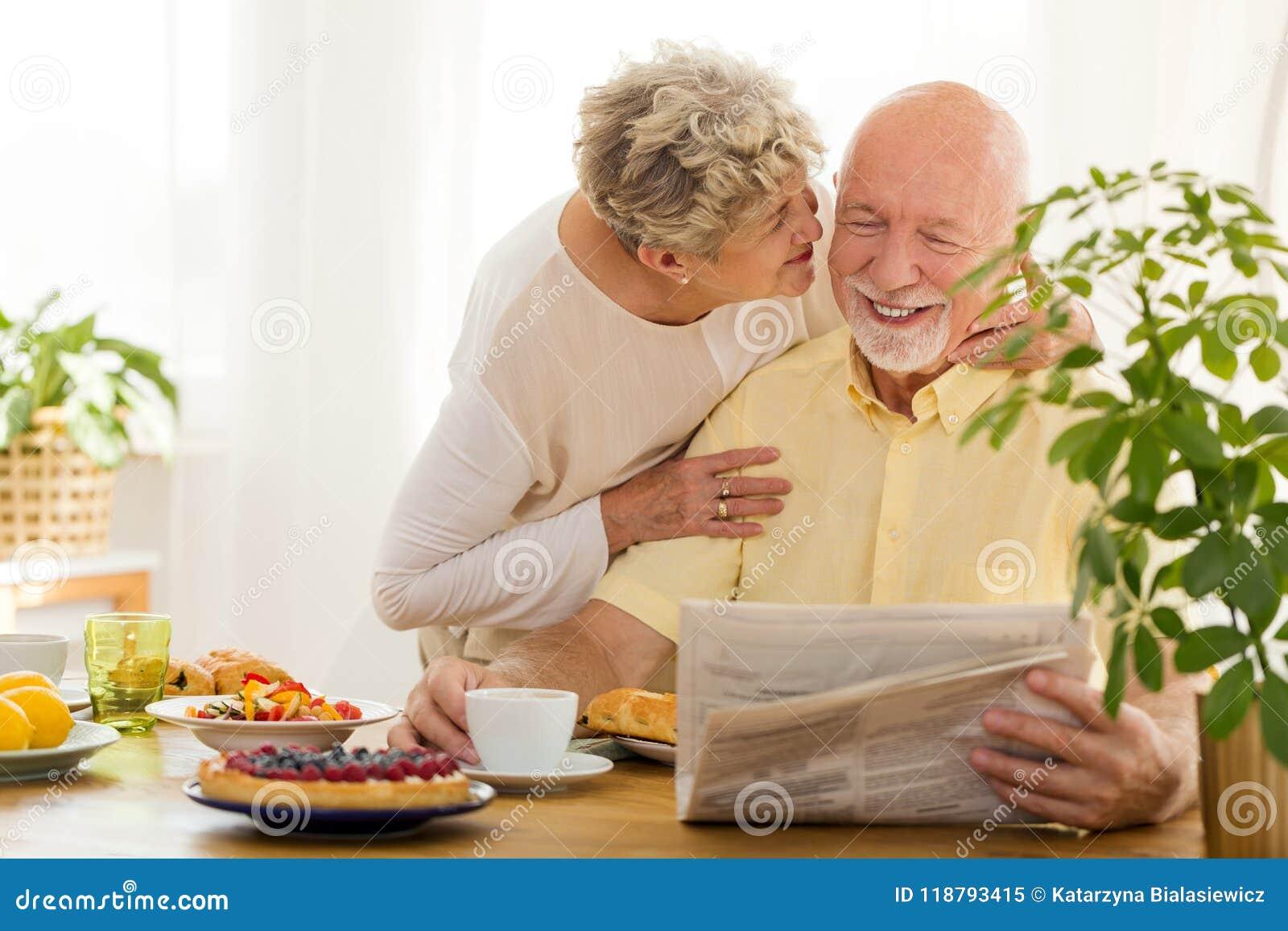 Jornal de sorriso da leitura do homem superior e sua esposa que beijam o