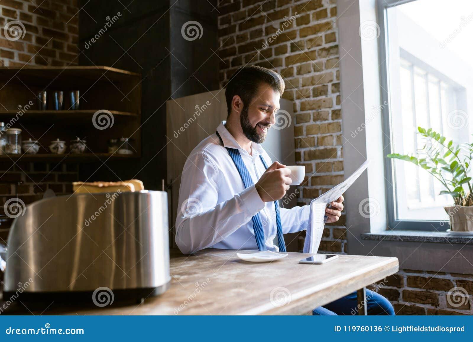 Jornal feliz da leitura do homem de negócios e café bebendo na cozinha