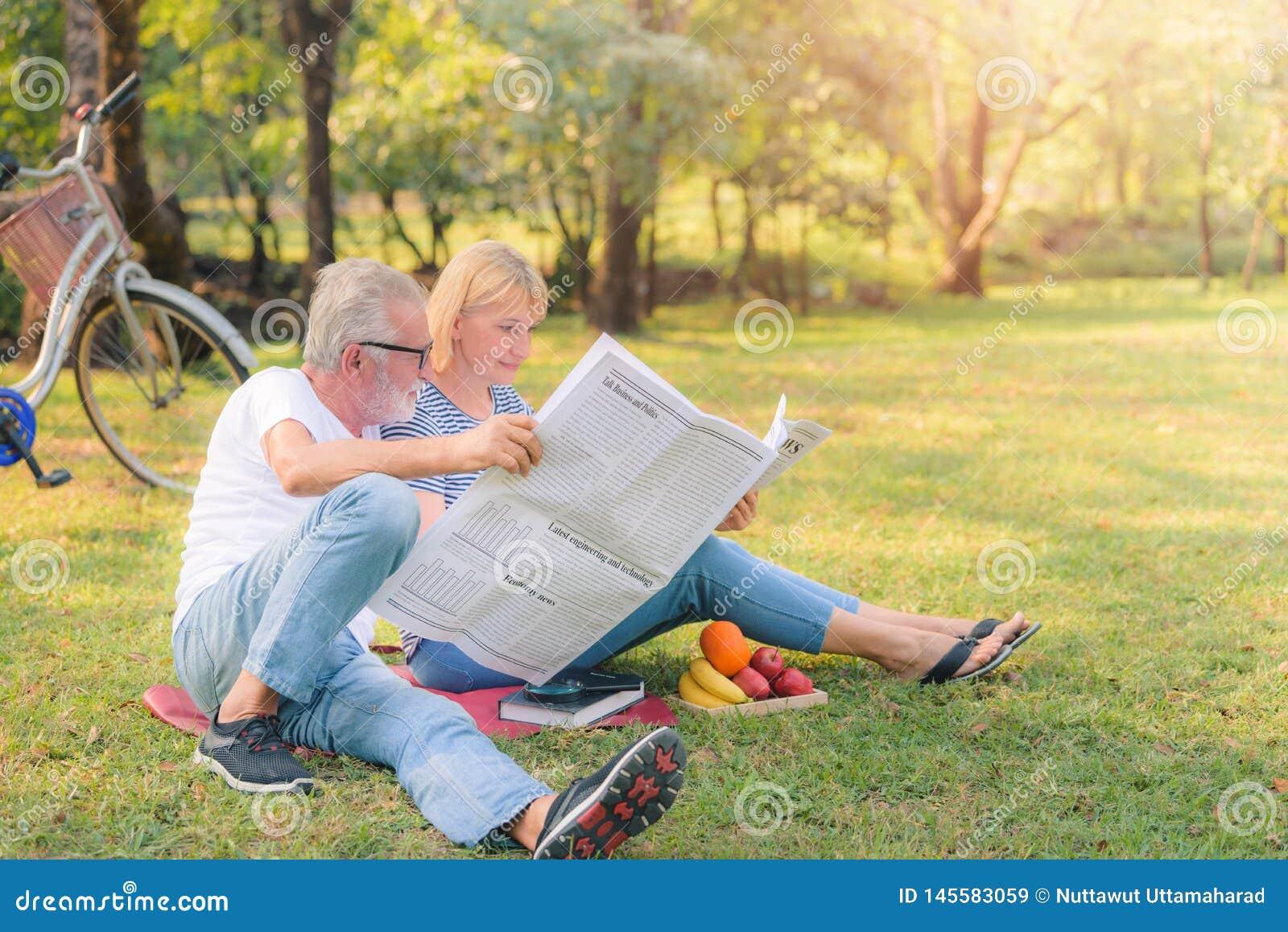 Jornal idoso da leitura dos pares no jardim no por do sol Amor da pessoa idosa dos pares do conceito