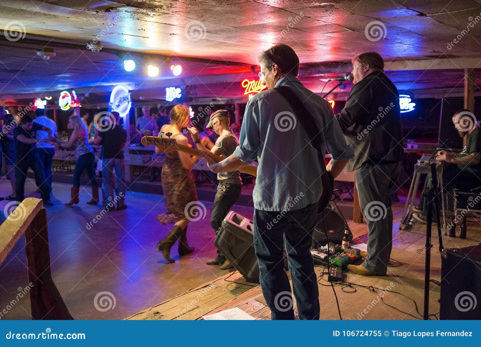 Jouer et personnes de bande de musique country dansant dans la salle de danse cassée de rai dans Austin, le Texas