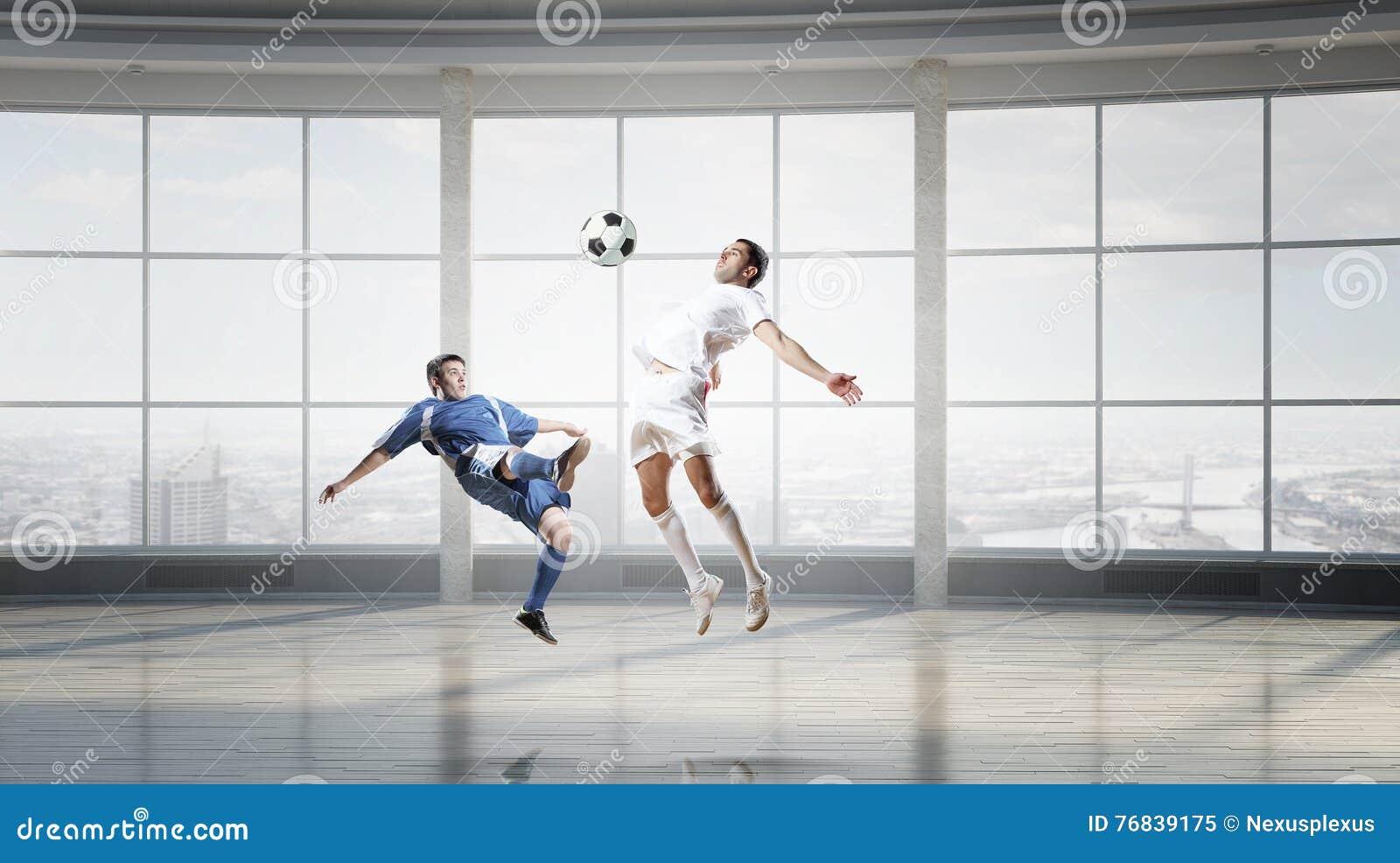 Jouer le football dans le bureau media mélangé image stock image