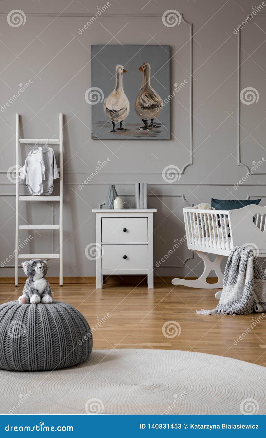 Jouet sur le pouf gris dans la chambre à coucher à la mode de bébé avec le berceau et les meubles en bois blancs, vraie photo ave