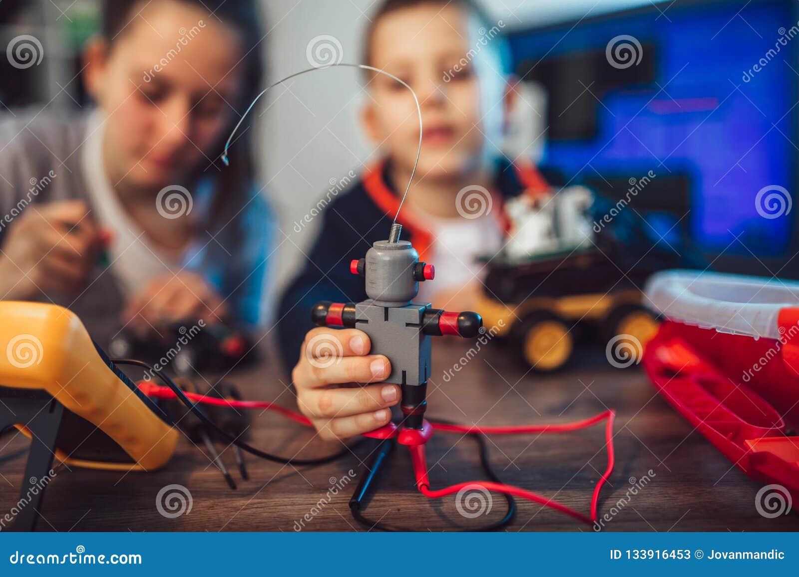 Jouet technique de sourire heureux de constructions de garçon et de fille et faire le robot