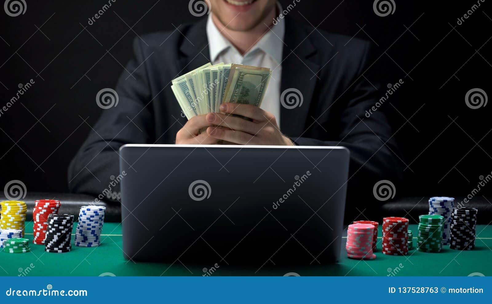 Joueur en ligne réussi de casino comptant l argent devant l ordinateur portable, gagnant parié