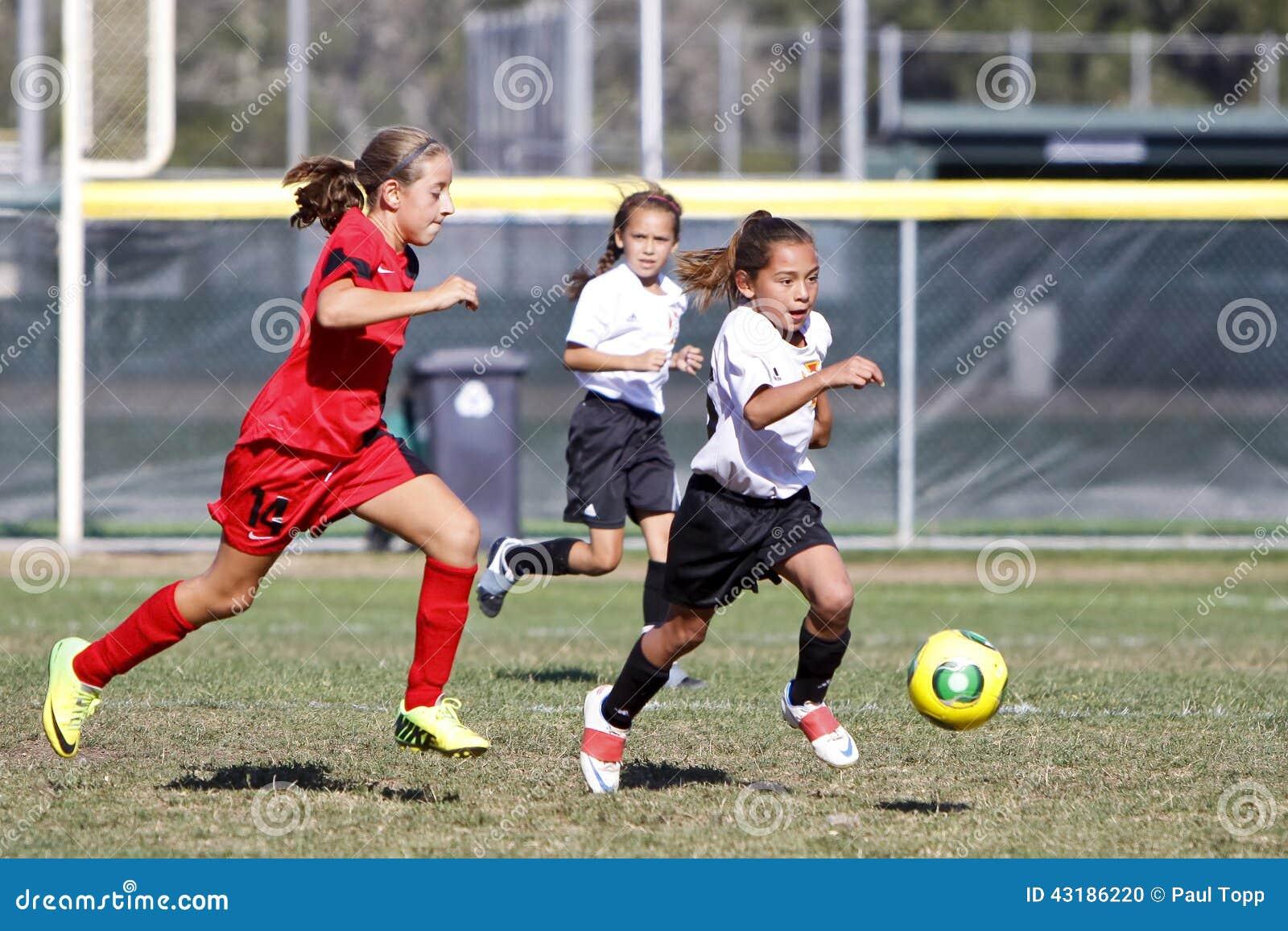 Joueurs de football du football de la jeunesse de filles courant pour la boule
