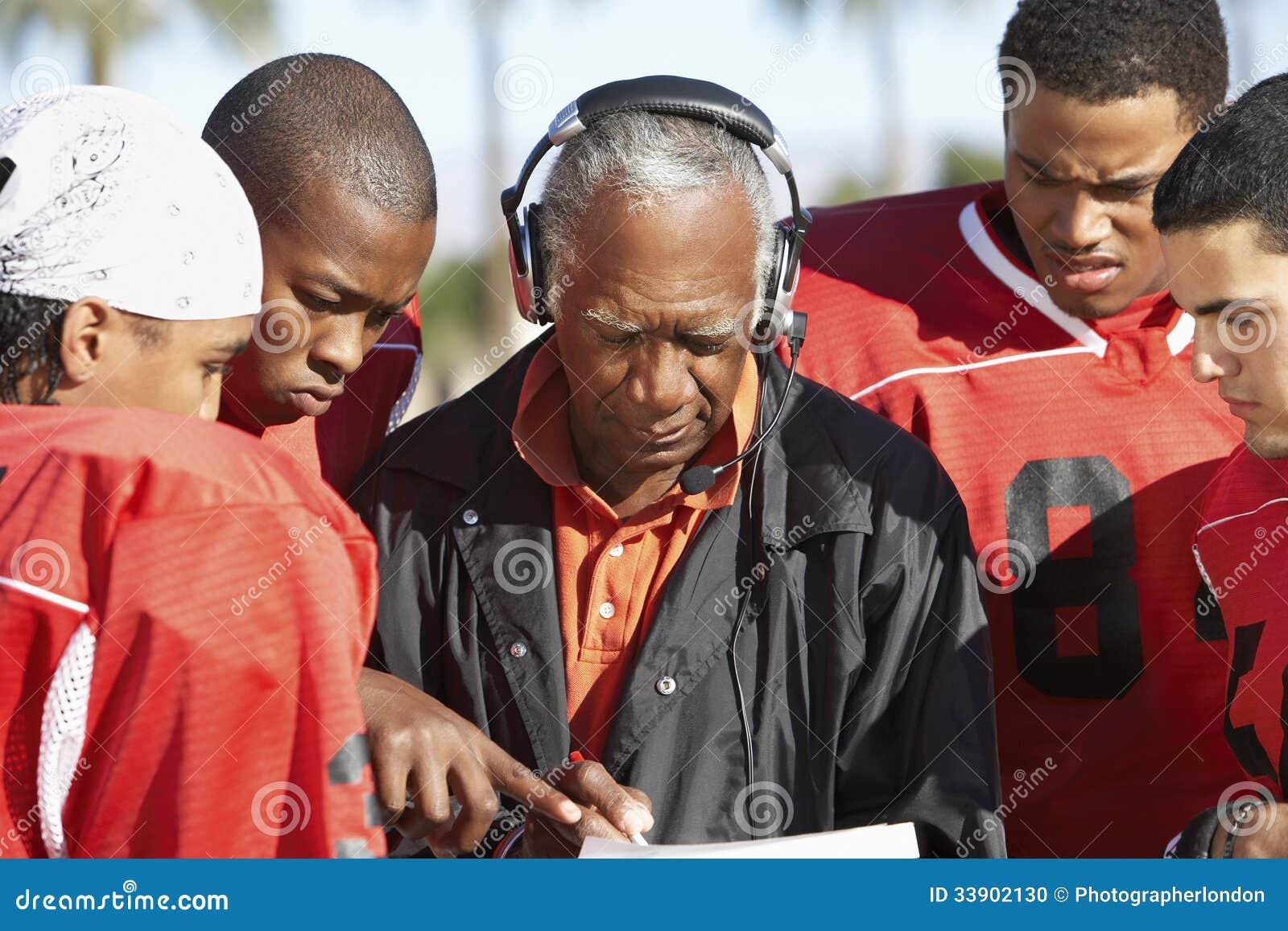 Joueurs de football et entraîneur Discussing Strategy