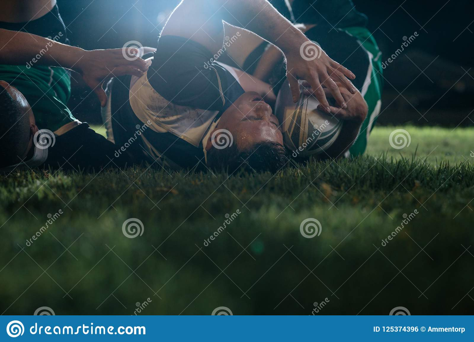 Joueurs de rugby luttant pour la boule au stade