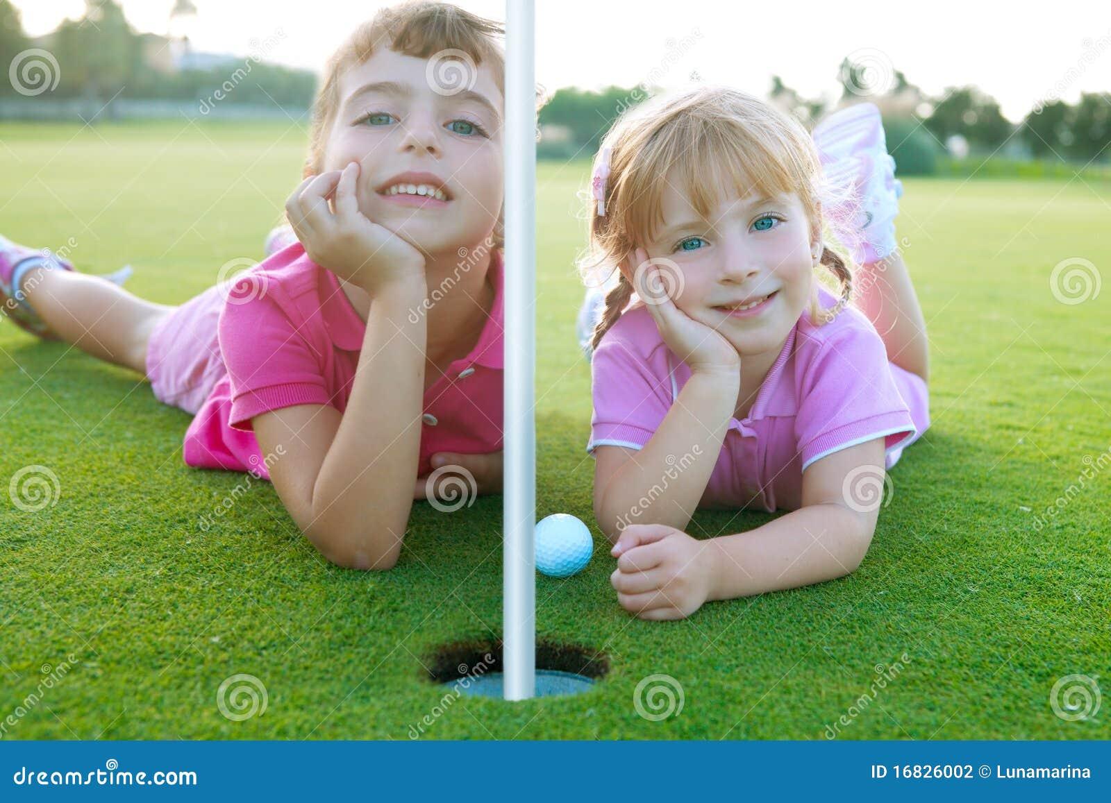 Jouez au golf les filles de soeur détendues en étendant la bille verte de trou