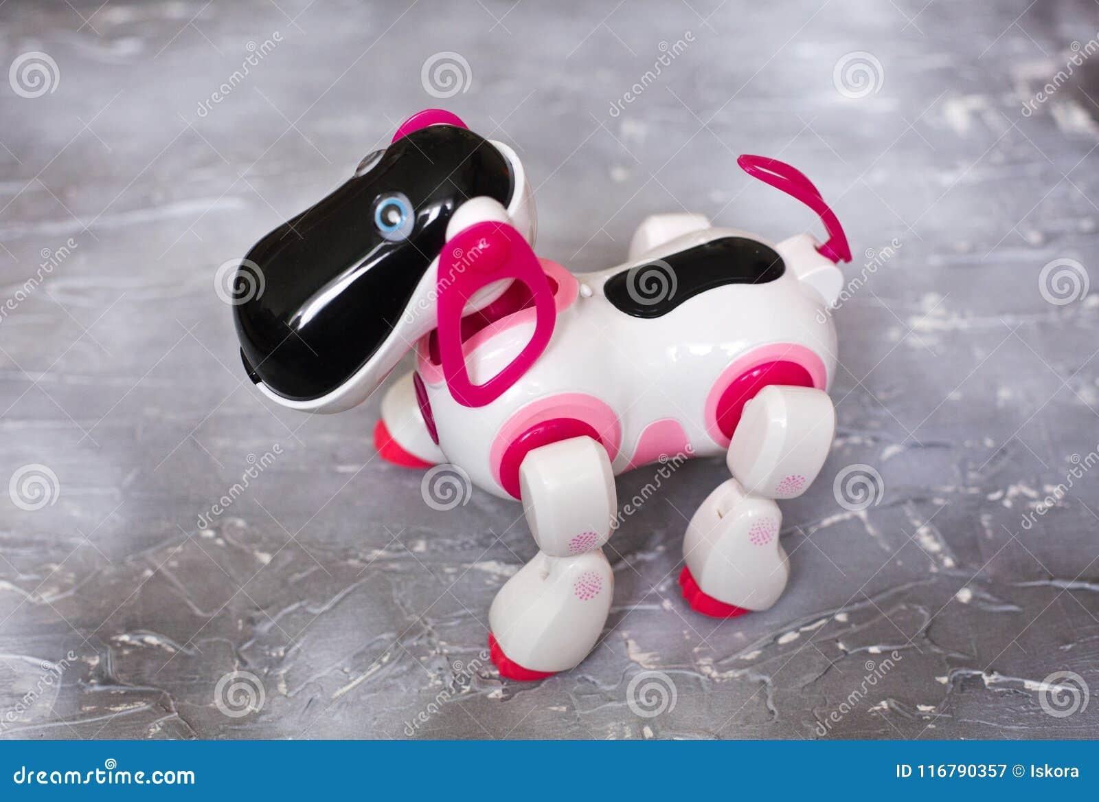 Jouez le robot blanc et rose, sur un fond concret Le chien est un robot