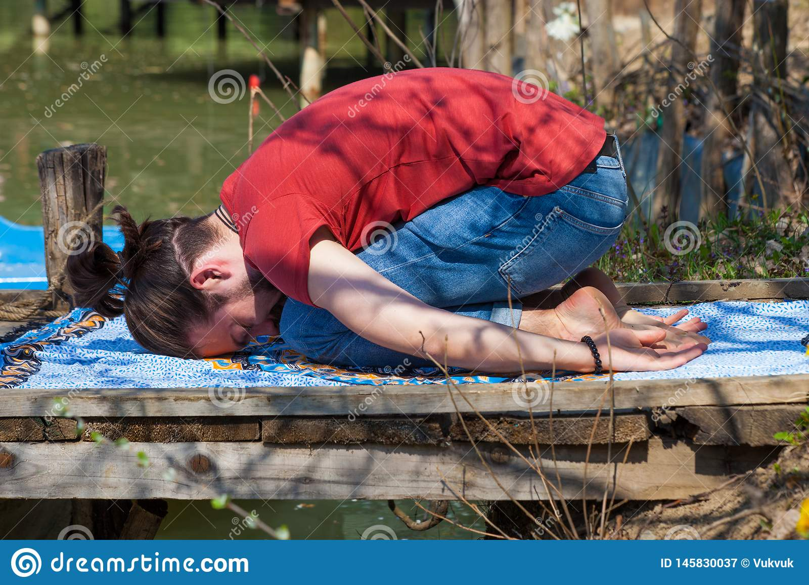 Jour d été de yoga de pratique en matière de jeune homme par la pose d enfant de lac pour la relaxation et le repos