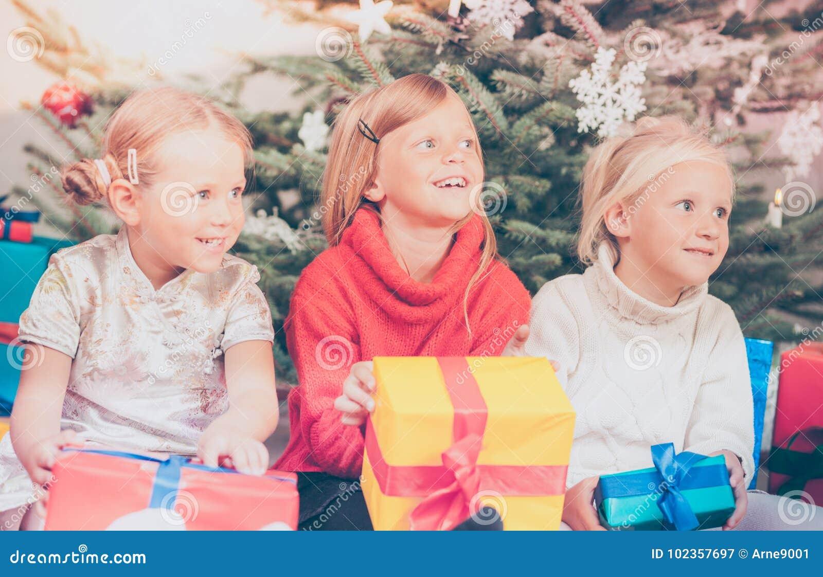 Jour de Noël dans la famille, les enfants déroulant des présents