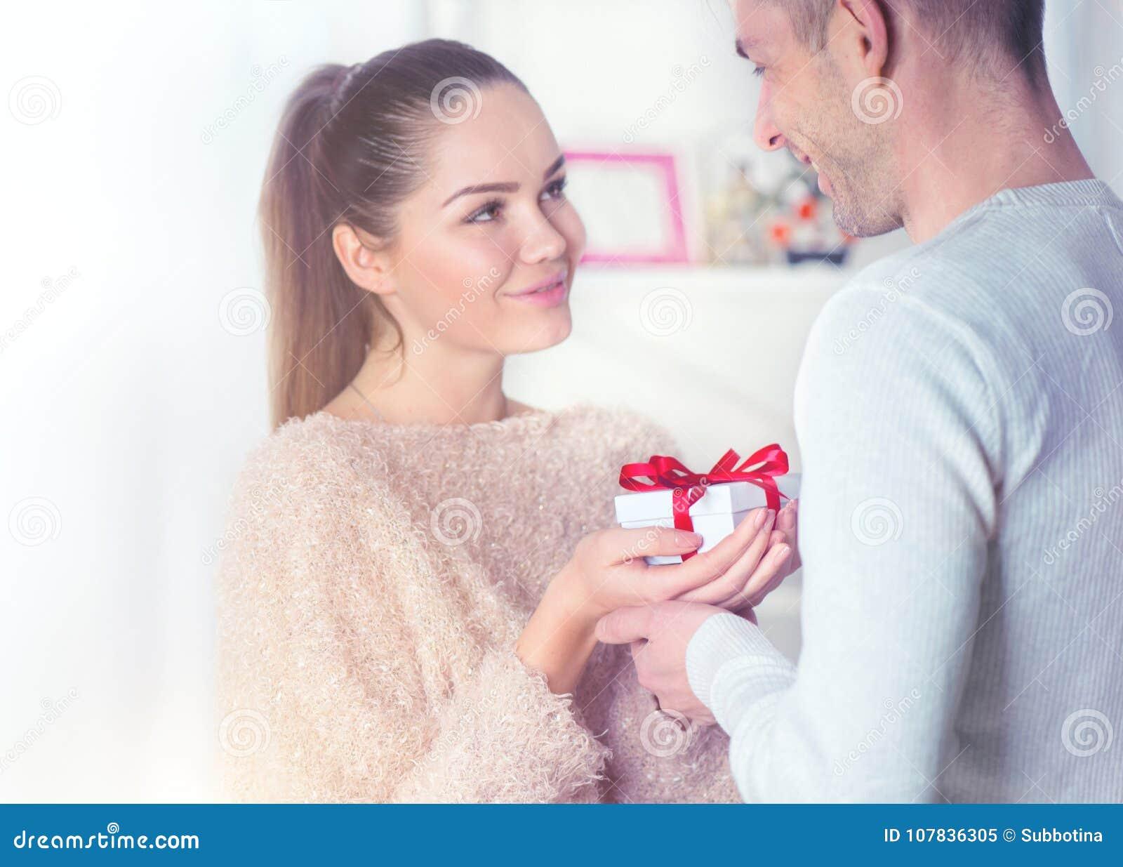 Jour du ` s de St Valentine Jeune homme donnant un cadeau à son amie