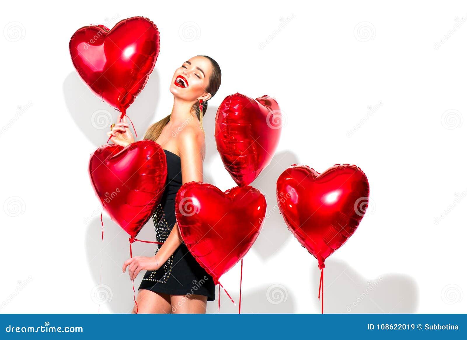Jour du `s de Valentine Fille de beauté avec les ballons à air en forme de coeur rouges ayant l amusement