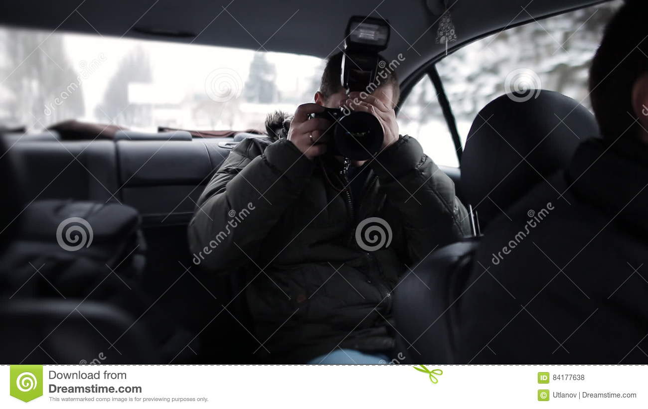 A Journalist Traveling In A Taxi With A Camera In Hand And Check The