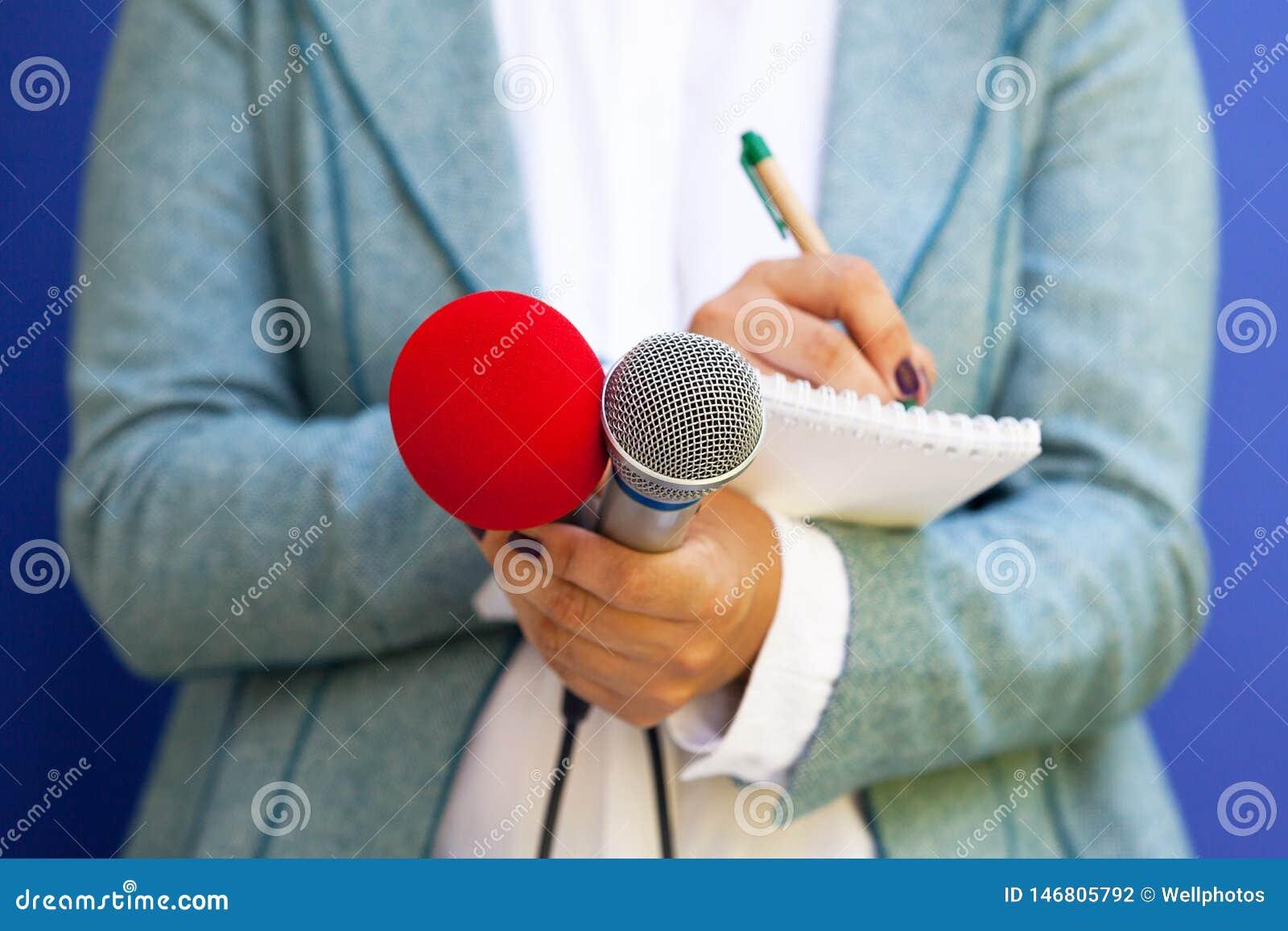 Journalista na conferência de imprensa, tomando as notas, guardando o microfone