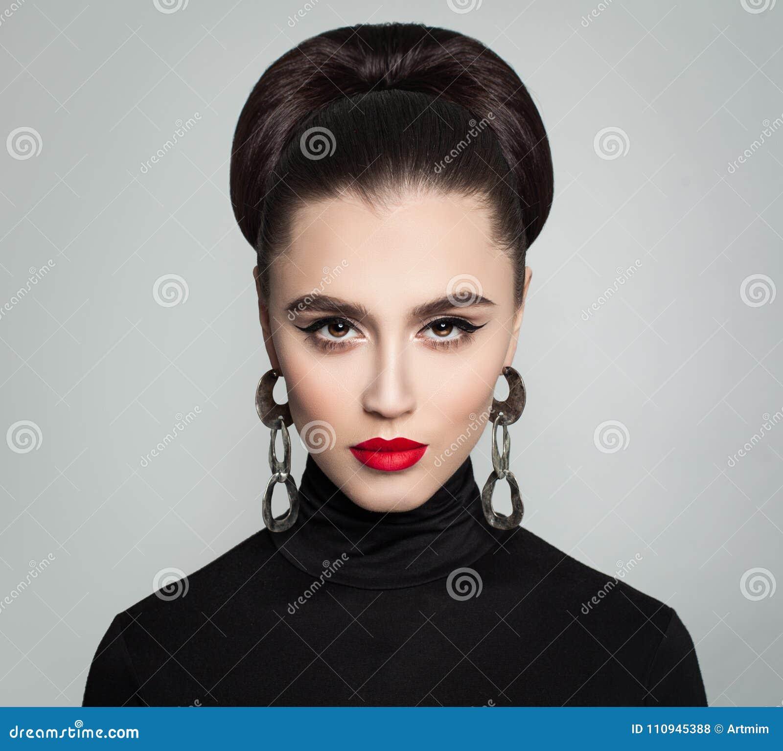 Jovem mulher à moda com penteado do bolo do cabelo