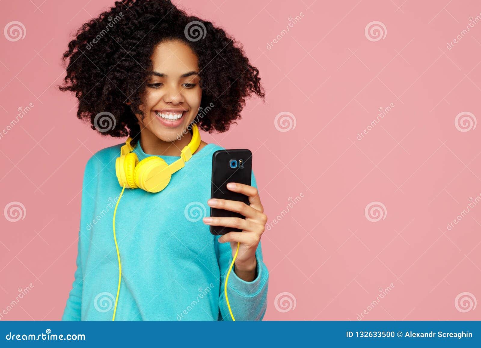 A jovem mulher afro-americano atrativa com sorriso brilhante vestida na roupa ocasional toma a imagem com smartphone sobre