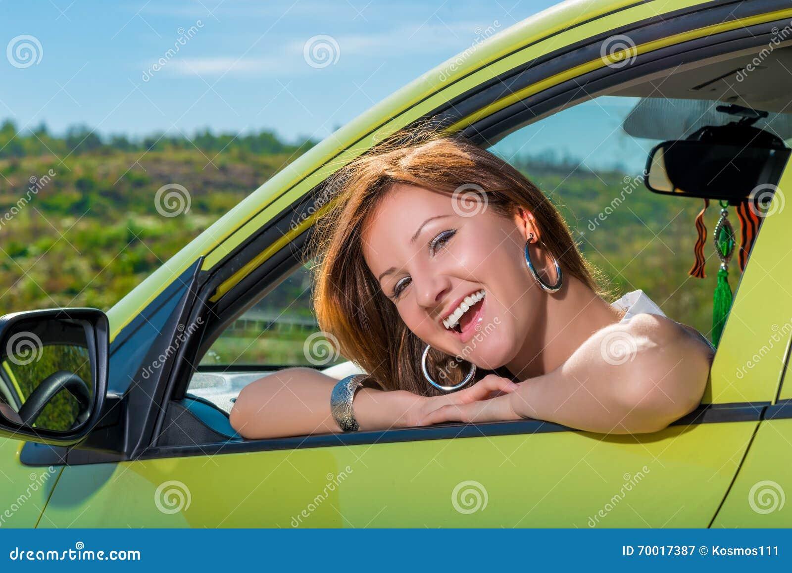 Jovem mulher alegre em um carro