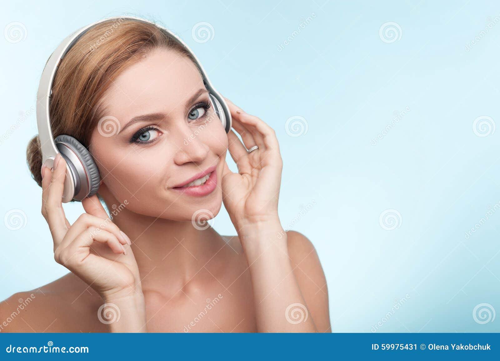 A jovem mulher alegre está usando fones de ouvido com alegria