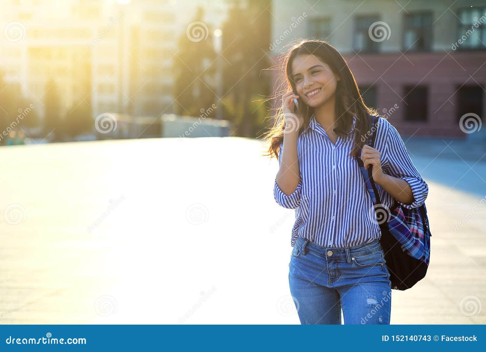 Jovem mulher alegre que fala pelo telefone fora com luz solar em seus cara e espaço da cópia