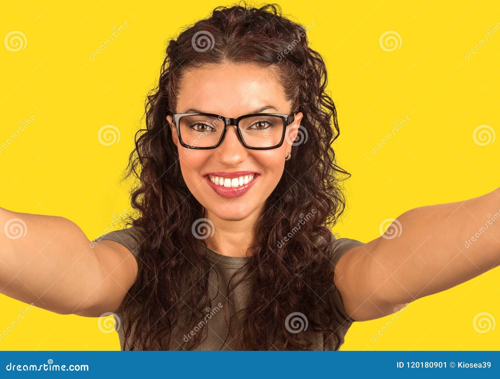 Jovem mulher alegre que olha a câmera e que toma um selfie