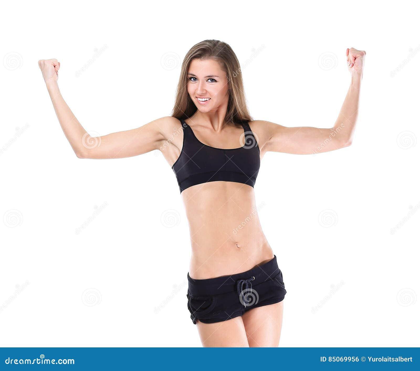 Jovem mulher alegre que sorri no sportswear que demonstra suas força e realizações no campo do esporte