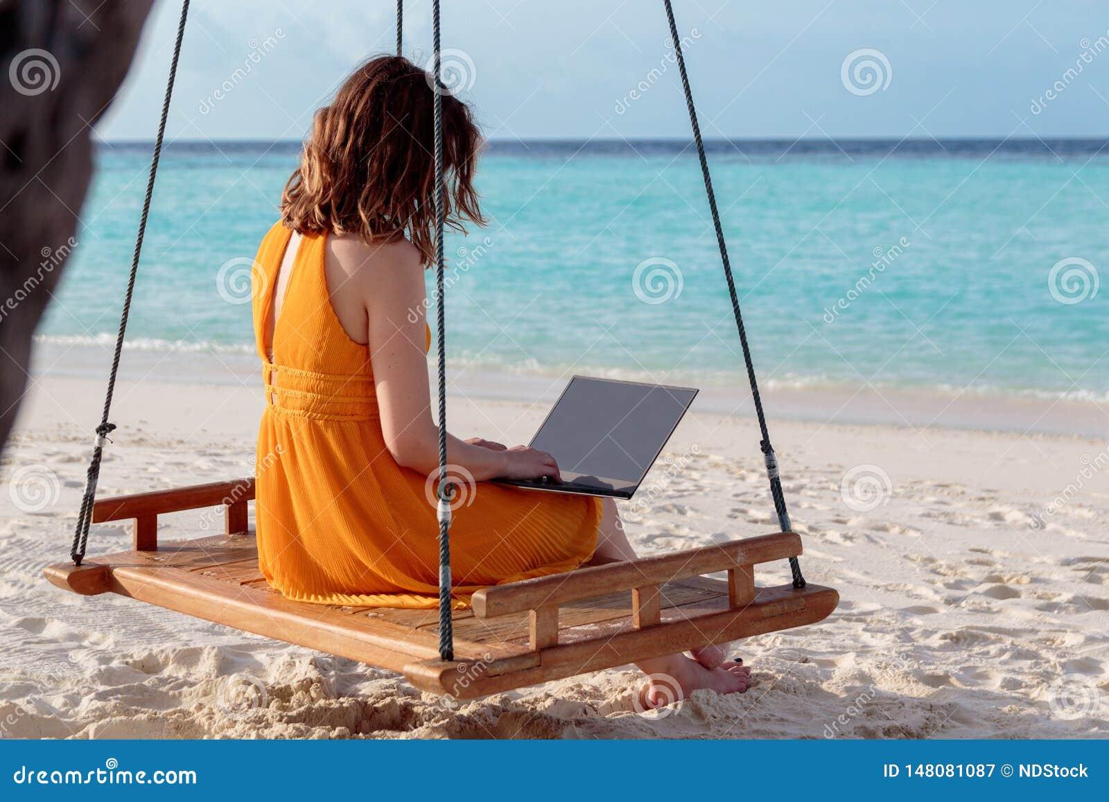 Jovem mulher assentada em um balanço e no trabalho com seu portátil ?gua tropical azul clara como o fundo