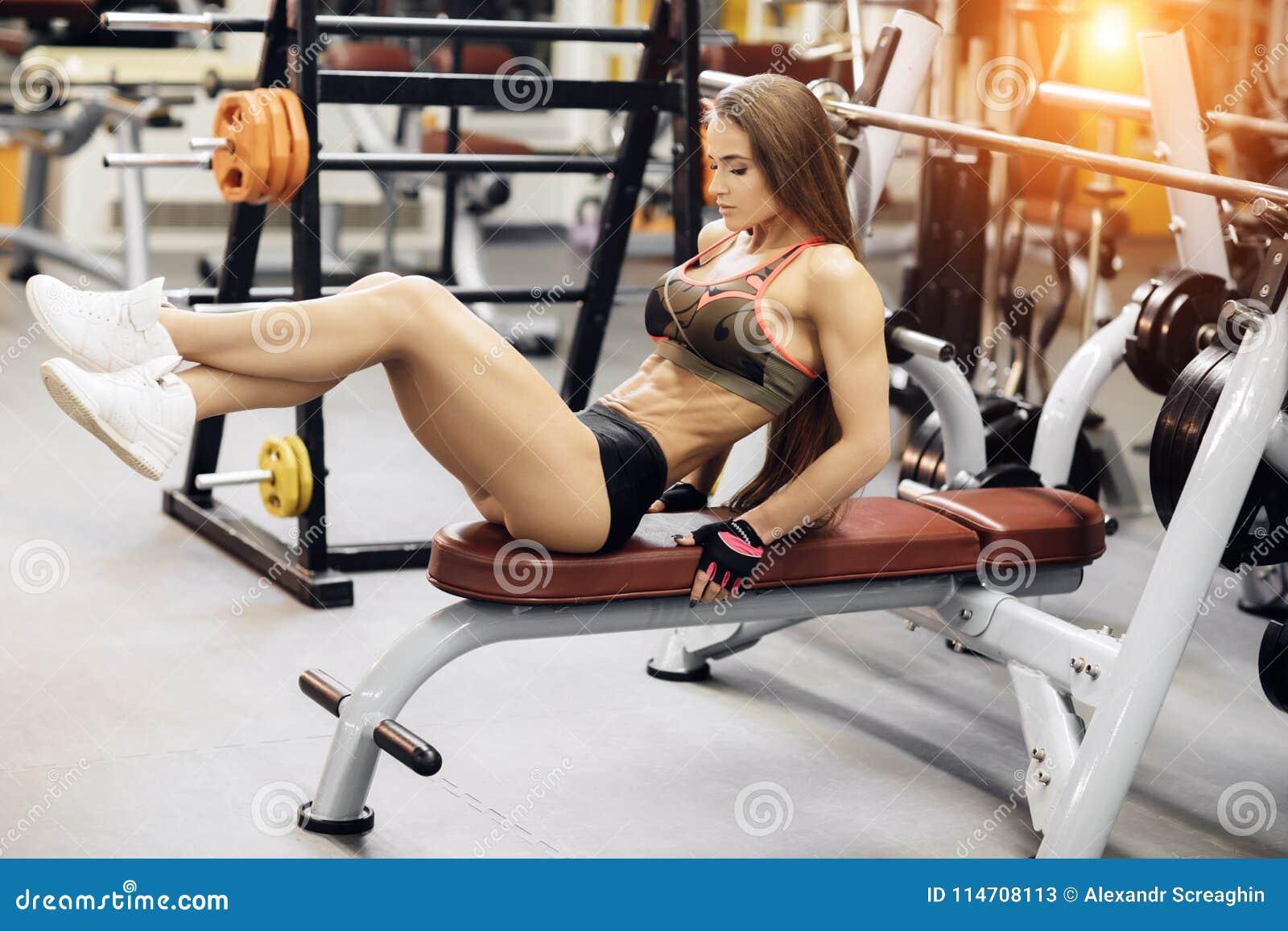 A jovem mulher atlética exercita para o Abs na imprensa de banco