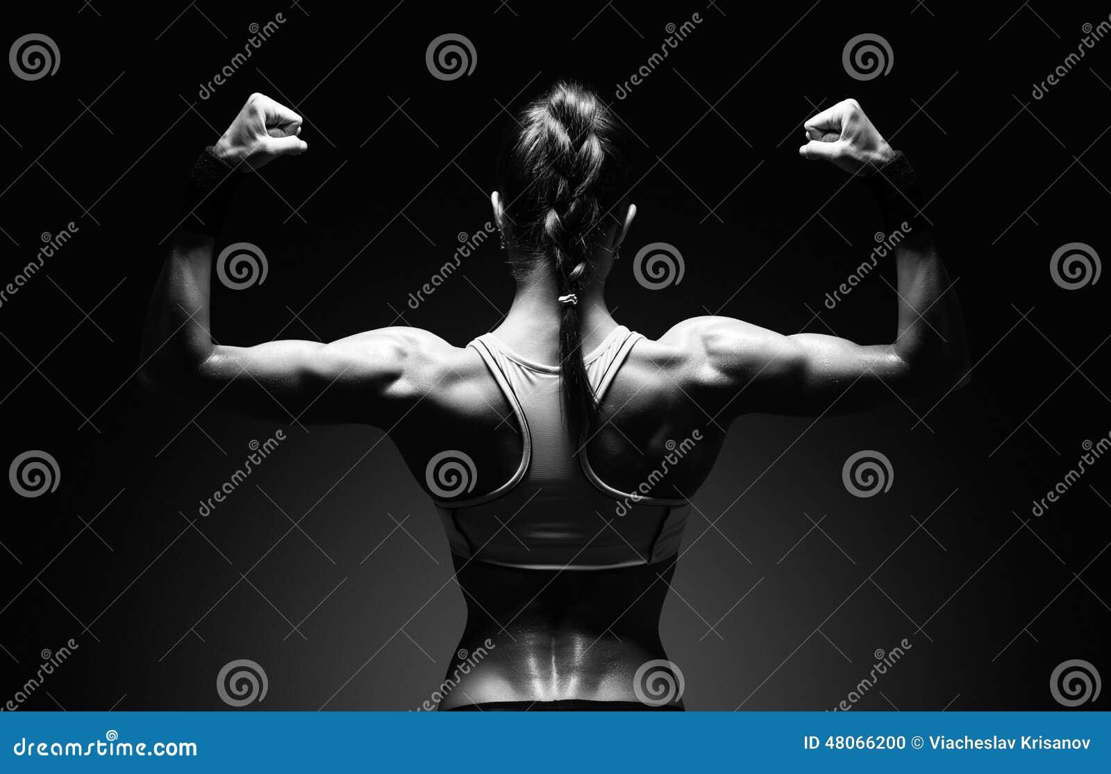 Jovem mulher atlética que mostra os músculos da parte traseira