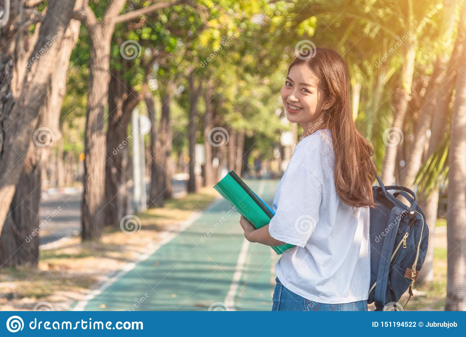 Jovem mulher atrativa alegre com trouxa e caderno e posição no parque