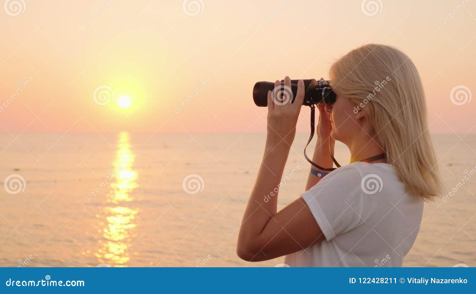 A jovem mulher atrativa olha através dos binóculos no nascer do sol sobre o mar Romance e aventura
