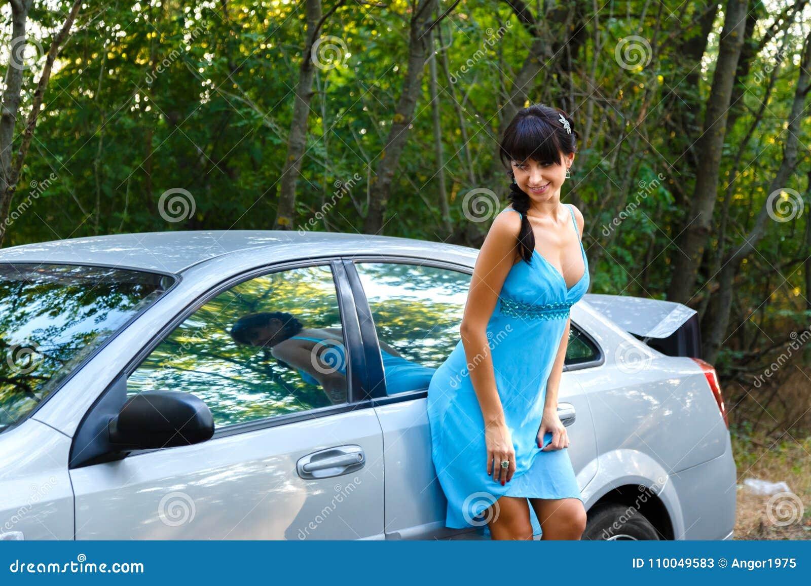Jovem mulher atrativa que está na estrada perto do carro branco