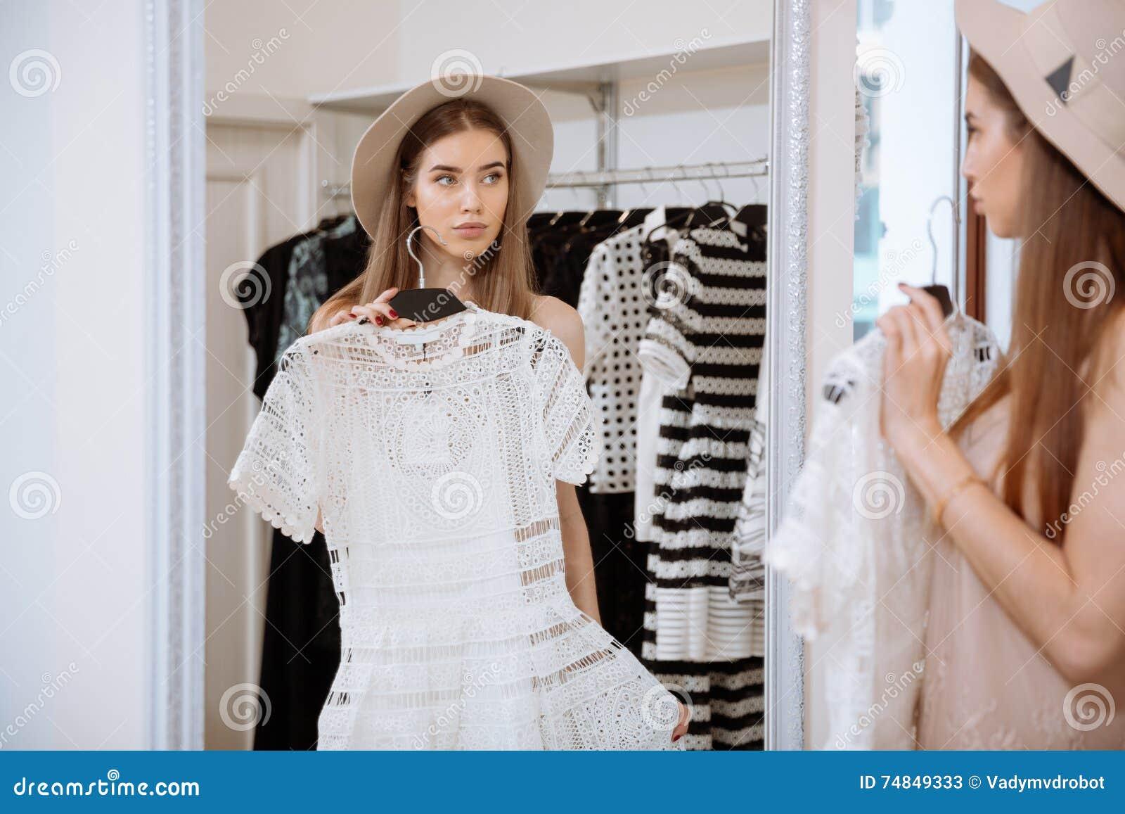 Jovem mulher atrativa que tenta no vestido na frente do espelho