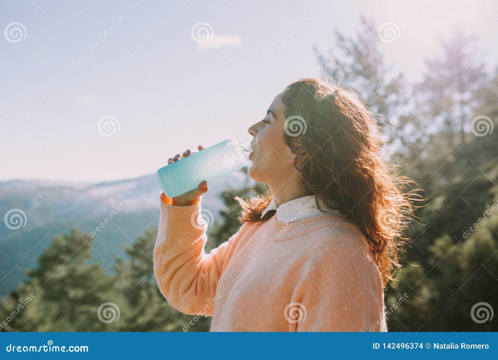 A jovem mulher bebe a água no meio da montanha